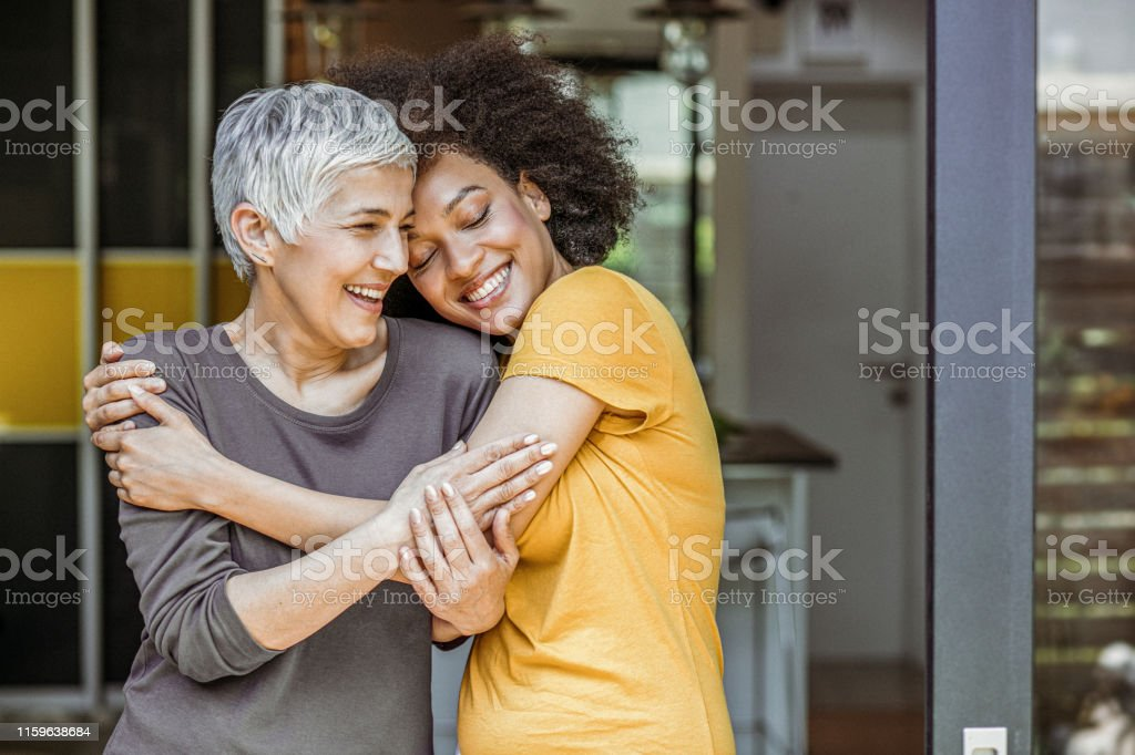 Two beautiful woman embracing Happy loving caucasian woman and grown millennial african woman laughing embracing. Active Seniors Stock Photo