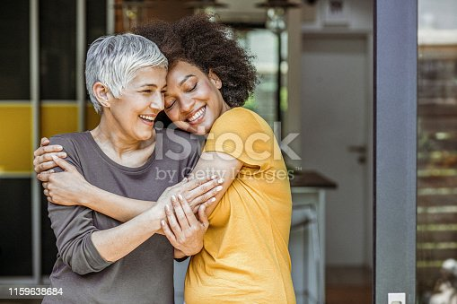Happy loving caucasian woman and grown millennial african woman laughing embracing.