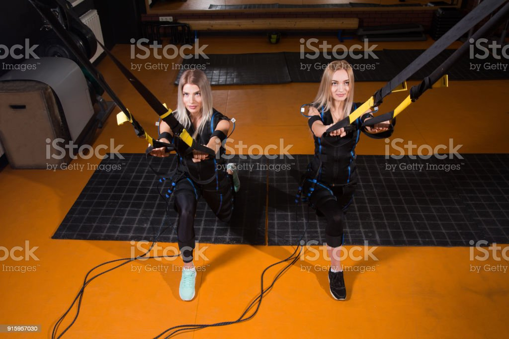 Two beautiful woman in Electrical Muscular Stimulation suit doing squat exercise for back and with suspension stock photo