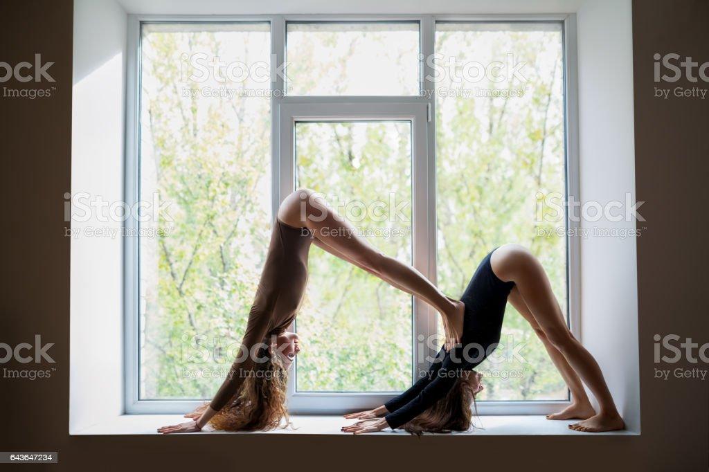 Two beautiful women doing yoga asana double downward dog on window sill stock photo