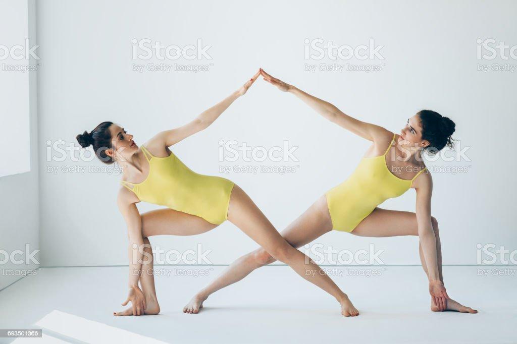 Two beautiful women doing yoga asana extended side angle pose stock photo