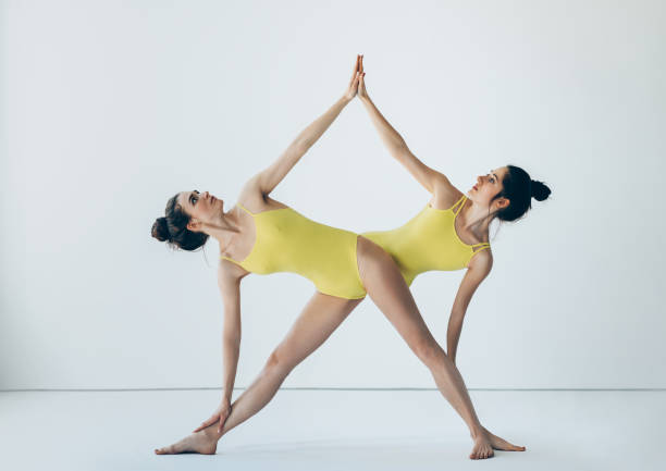 Deux belles femmes faisant triangle prolongée d'asana yoga pose - Photo
