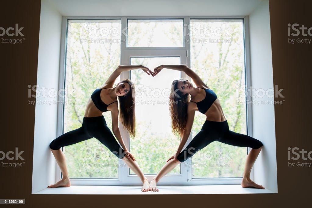 Zwei schöne Frauen, die Yoga Asana zeigt Herz-Symbol auf der Fensterbank – Foto