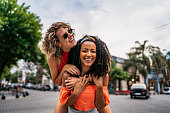 Two young beautiful smiling Argentinian women having fun at city street, having a piggyback ride. Shooting Buenos Aires, Argentina.
