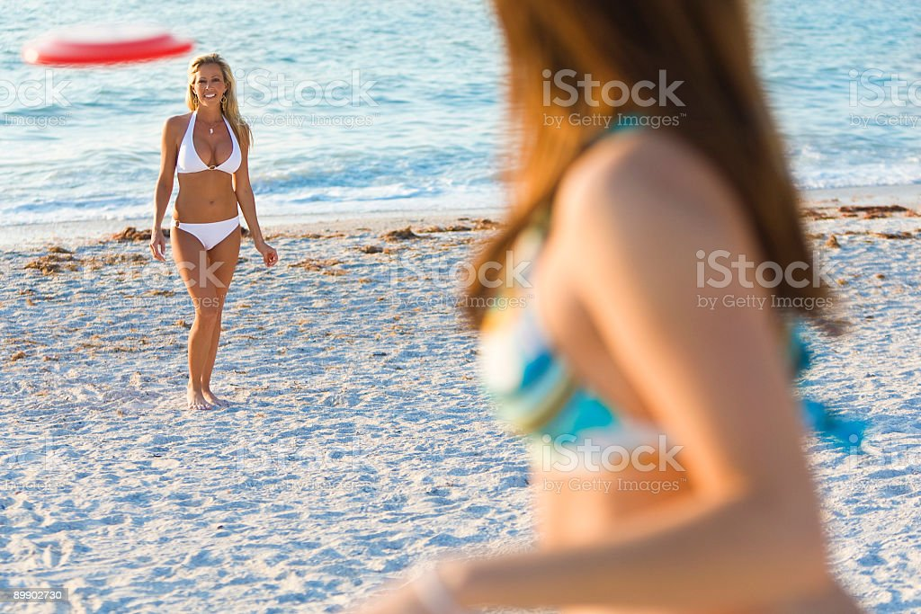Two Beautiful Women in Bikinis Playing Frisbee At The Beach royalty-free stock photo