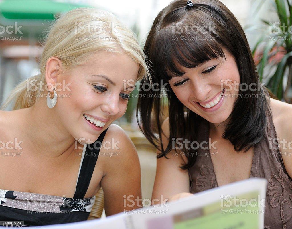 Zwei schöne Frauen im Freien mit Blick auf das Menü – Foto