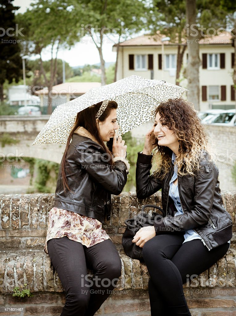 Two beautiful women talking under umbrella royalty-free stock photo