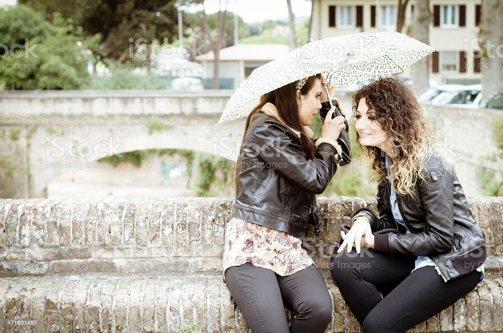 Two beautiful women talking under umbrella royalty-free stock photo