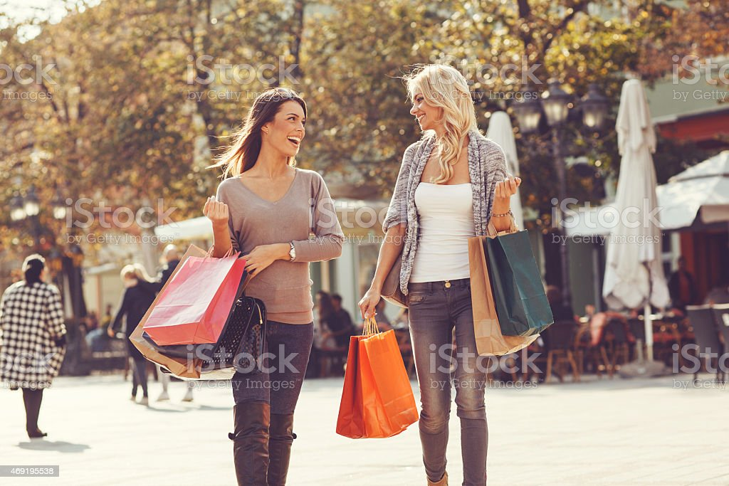 Two beautiful women walking down the street after shopping stock photo