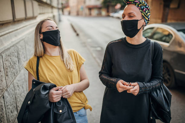 Two beautiful women with black face masks laughing on the street