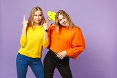 鮮やかな服で2人の美しい若いブロンドの双子の姉妹の女の子