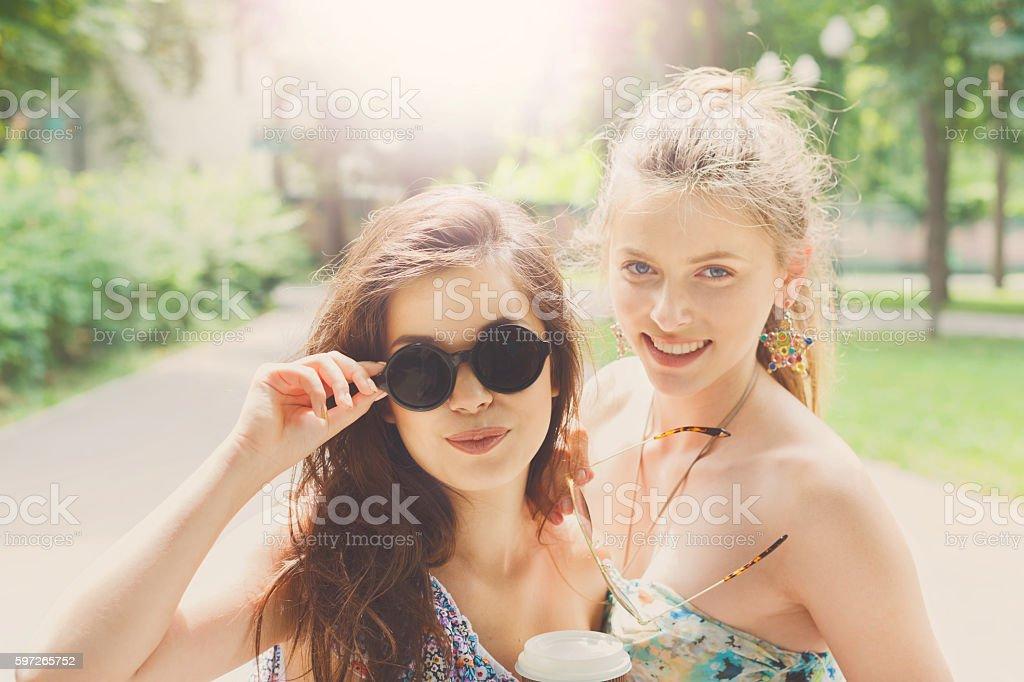 Two beautiful young boho chic stylish girls walking in park. Lizenzfreies stock-foto