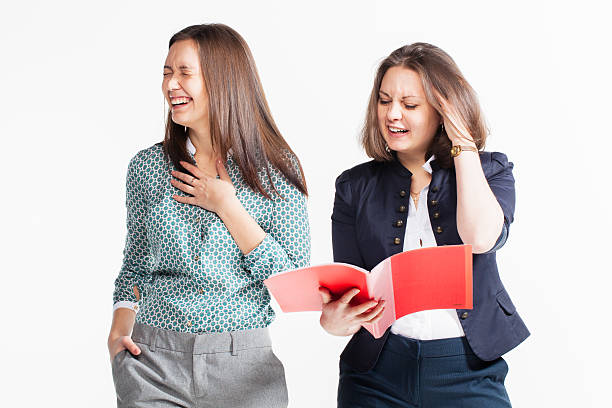 Two beautiful young business women laughing and holding files stock photo