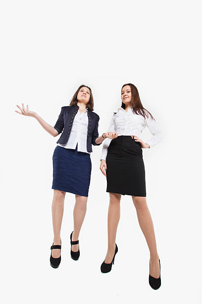 Two beautiful young business women standing and talking stock photo