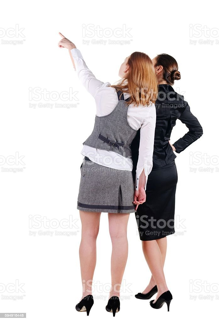 Two beautiful young bussineswoman looking at wall. Rear view. Is stock photo