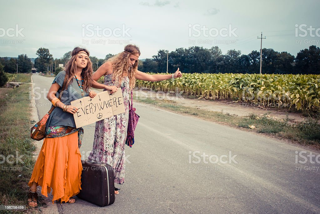 Two beautiful young hippie friends hitchhiking royalty-free stock photo