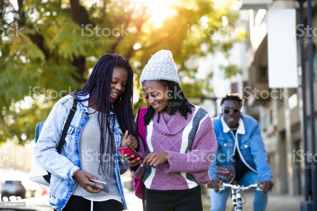Two beautiful young woman using mobile phone in the street. stock photo