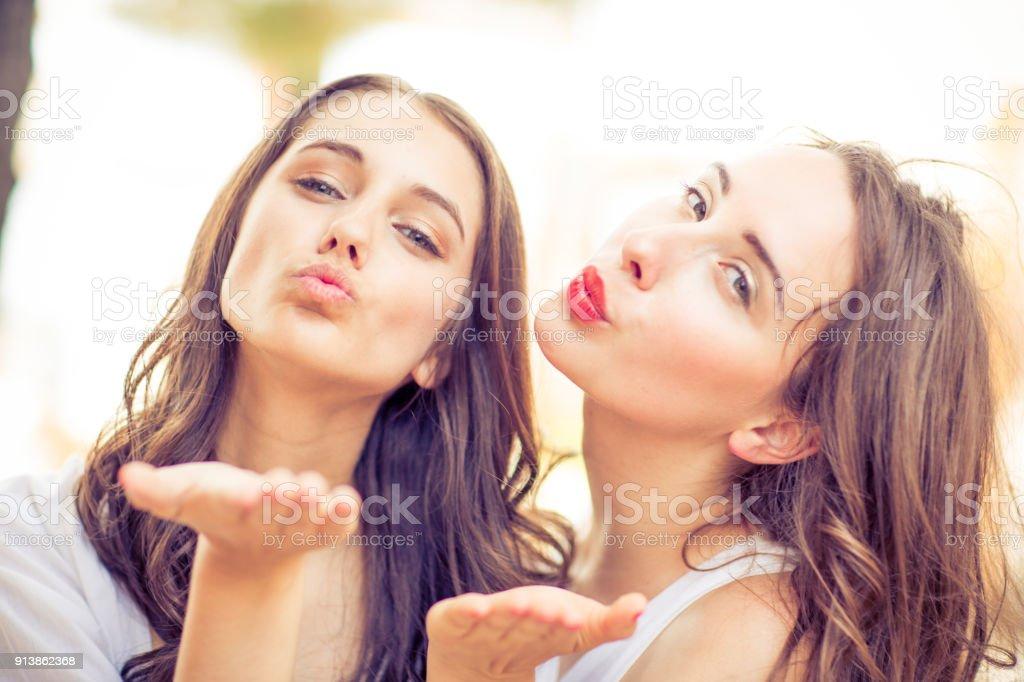 Two Beautiful Young Women Blowing A Kiss Stock Photo