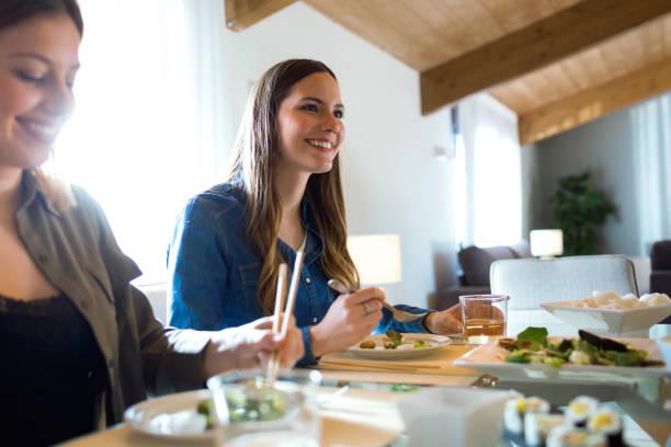 家で日本食を食べている2人の美人若い女性。 - ライフスタイル ストックフォトと画像