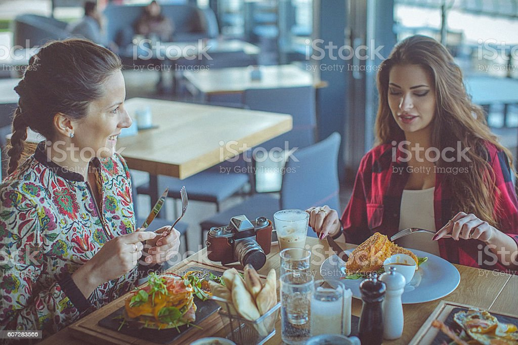 Two beautiful young women have breakfast at a fancy restaurant stock photo