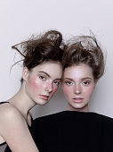 Two beautiful young women look alike sisters with creative artistic make-up and hairstyle Close-up Faces portrait Studio shot