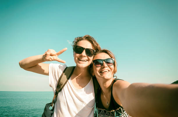 Deux belles jeunes femmes qui selfie sur la plage - Photo