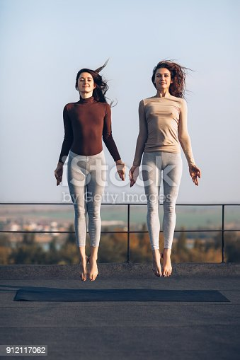 istock Two beautiful young women synchronously jump on the roof outdoors 912117062
