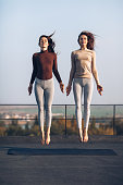 Two beautiful young women synchronously jump on the roof outdoors. Girlfriends are engaged in acrobatics and yoga. Frozen jumping women