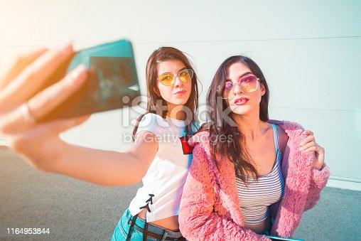 Two beautiful young women taking a selfie