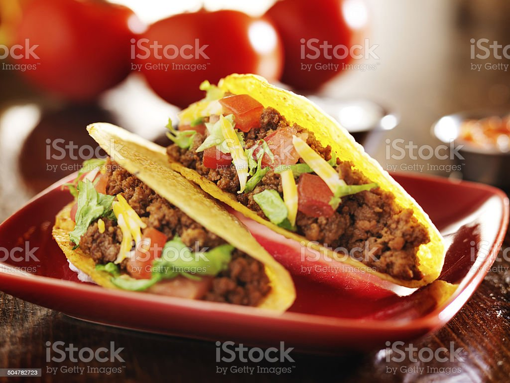 two beef hard shell tacos with cheese, lettuce and tomatoes stock photo