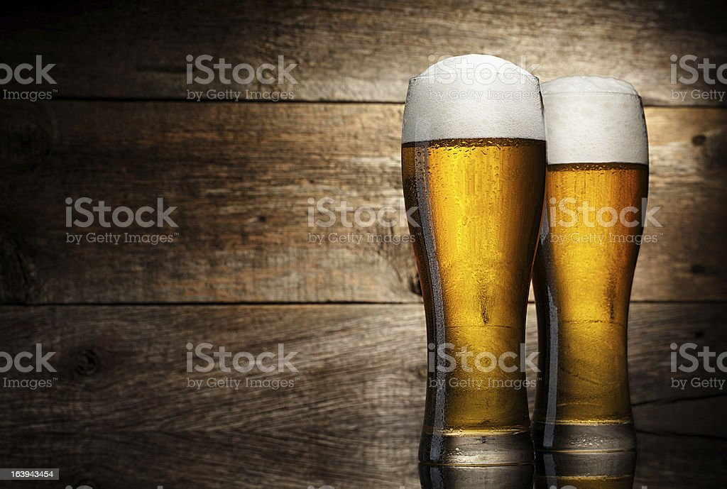 Dos vaso de cerveza en una mesa de madera y fondo - Foto de stock de Bebida libre de derechos