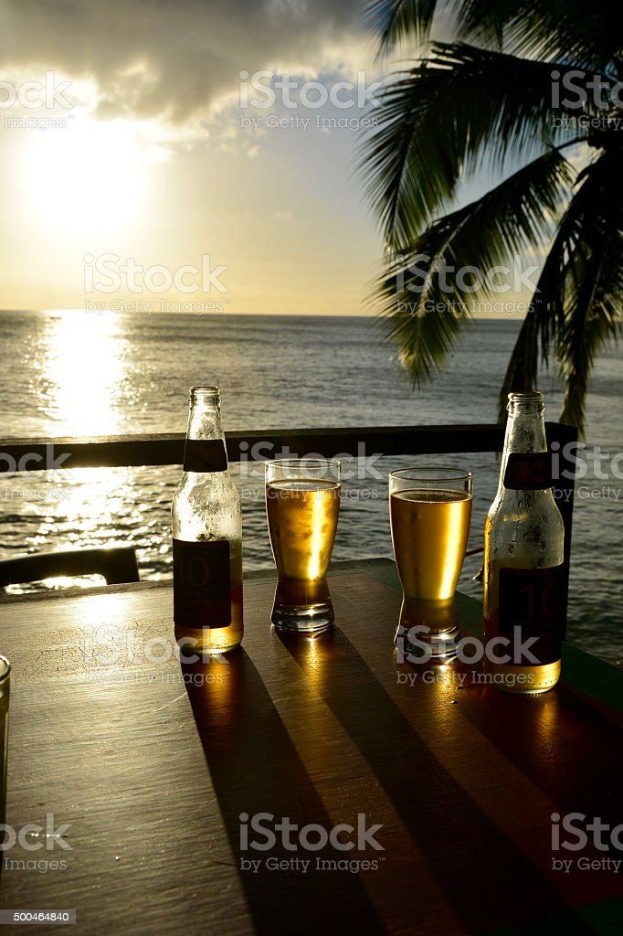 Two beers over sunset beach stock photo