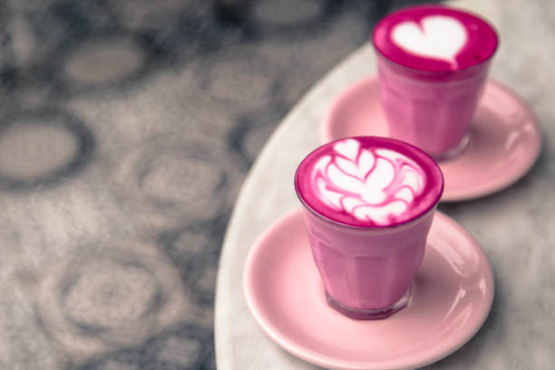 two beetroot color latte are on marble background. - caffè latte foto e immagini stock