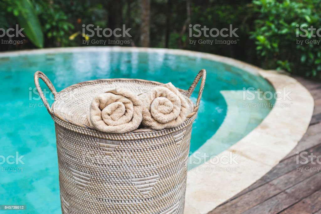 Two beige rolled towels in wicker basket near private pool with turquoise clear water stock photo