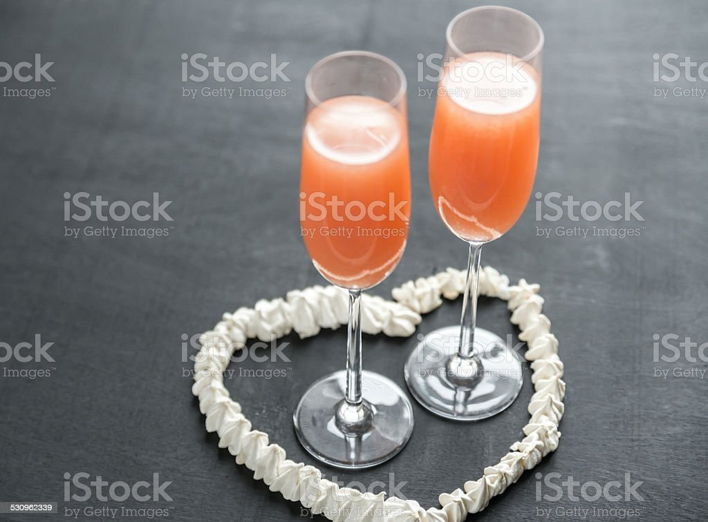 Two bellini cocktails inside of meringue heart stock photo