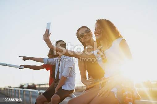 503545320istockphoto Two best female friends are taking a picture of them selves while their partners are looking at a sight view. 1028882646