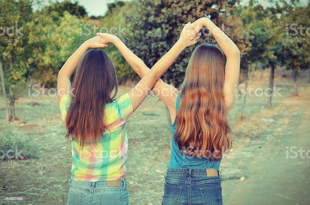 Two best friend girls making a forever sign stok fotoğrafı