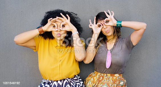 Attractive mixed race friends in their late 30's holding their fingers around their eyes like glasses