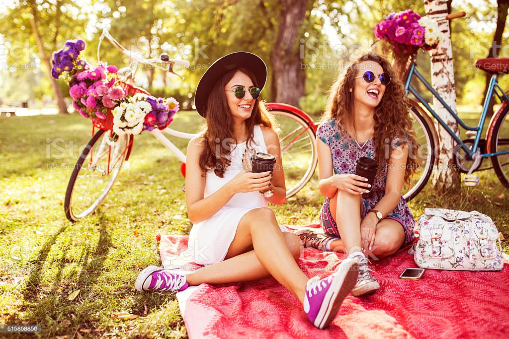 Two best friends drinking coffee to go in nature stock photo