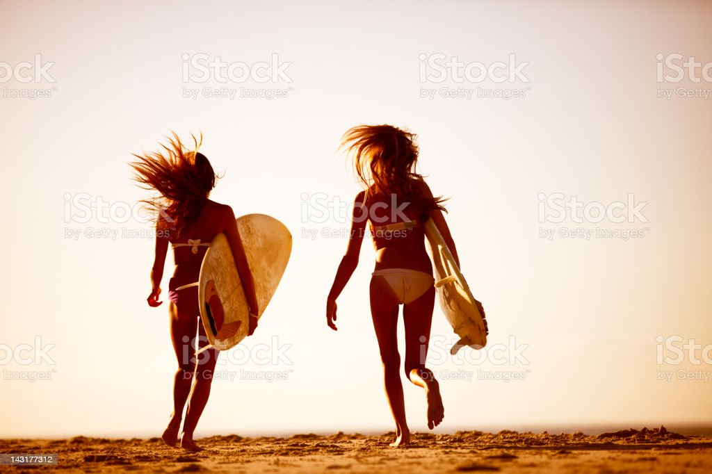 Two best friends going for a surf together royalty-free stock photo