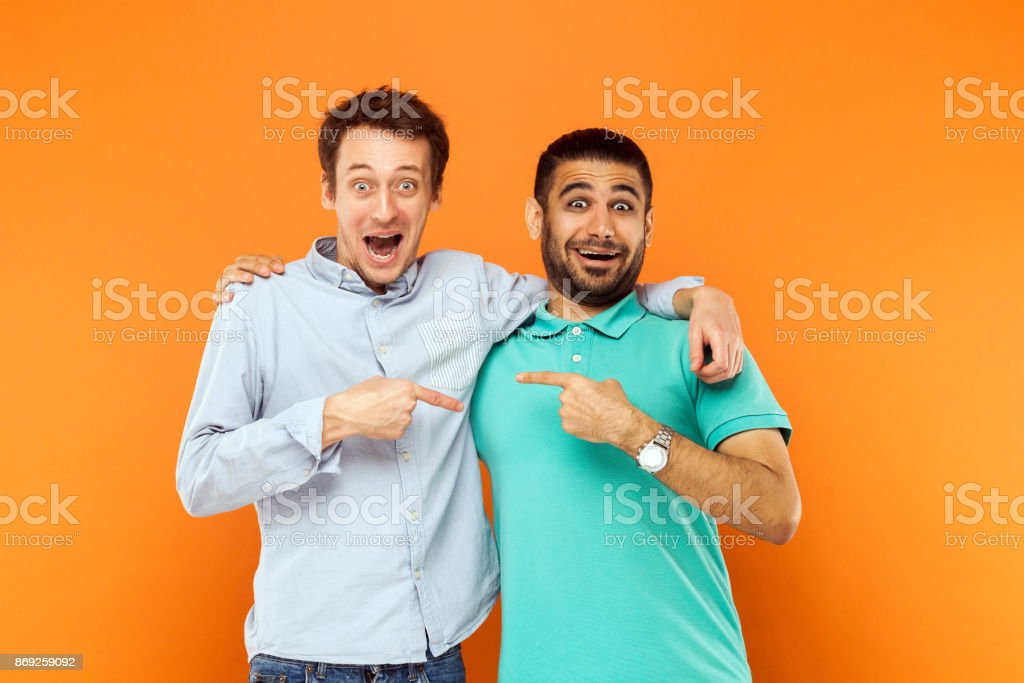 Two best friends hugging, pointing finger each other and looking at camera with shocked face foto stock royalty-free