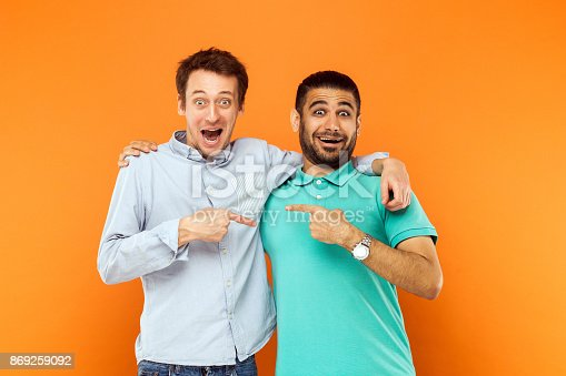 istock Two best friends hugging, pointing finger each other and looking at camera with shocked face 869259092