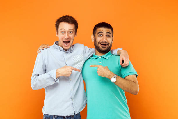 Two best friends hugging, pointing finger each other and looking at camera with shocked face stock photo
