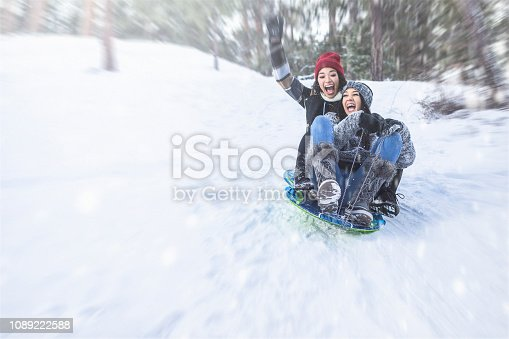 Two woman on a winter vacations playing in the snow.