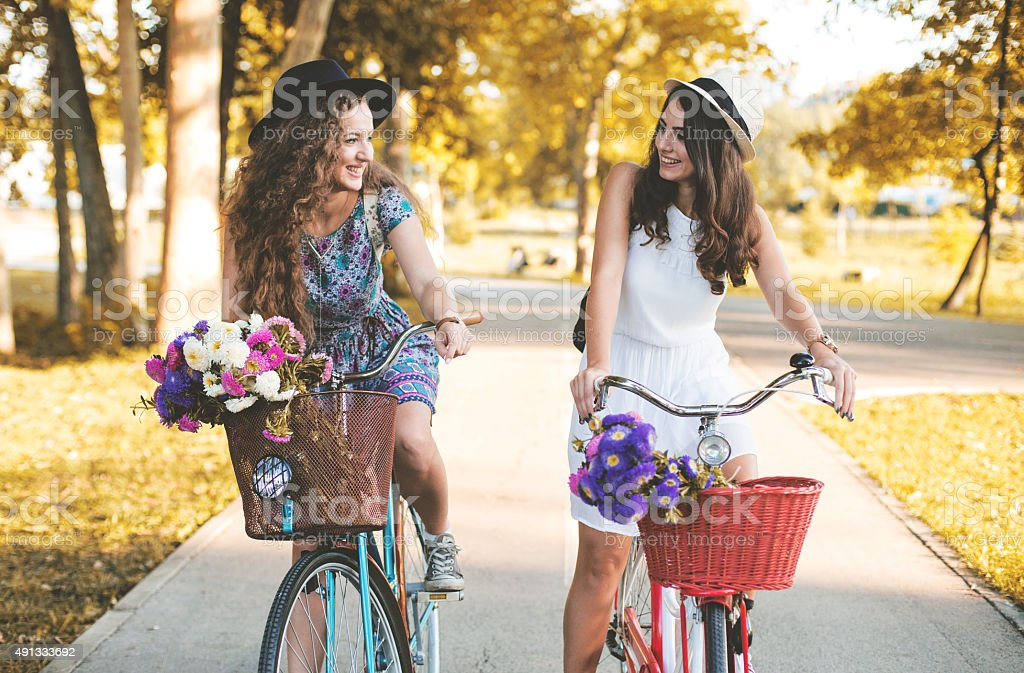 Two best friends riding bicycles in a park stock photo