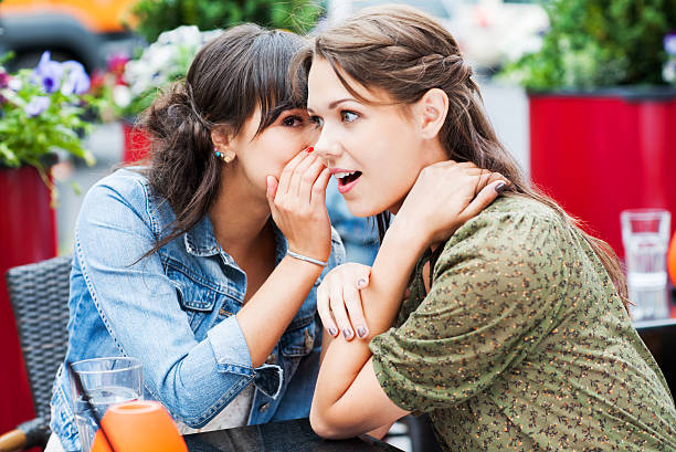 Two best friends sitting in a cafe and gossiping, stock photo
