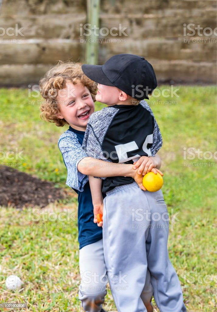 Two best friends, young boys, celebrate after winning a baseball stock photo