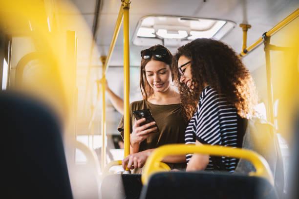 två bästa unga söta flickan vänner står i en buss och tittar i en telefon. - spårvagn bildbanksfoton och bilder