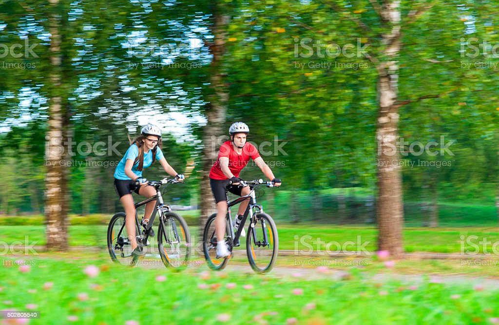 Two Bicycle Riders Having Time Together Outdoors in Summer Forest. stock photo