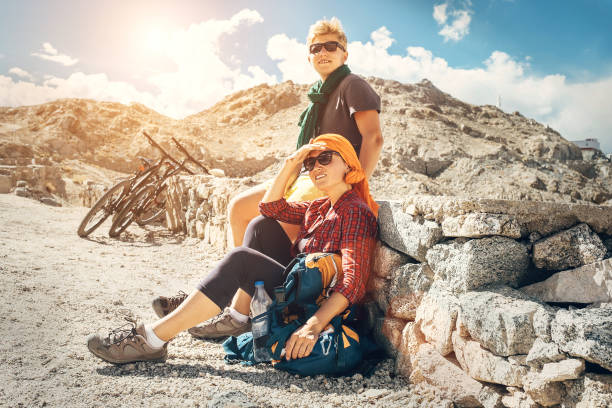 Two bicycle travelers rest on mountain road Two bicycle travelers rest on mountain road female biker resting stock pictures, royalty-free photos & images